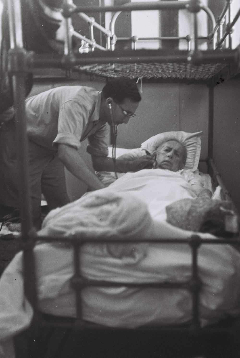 A doctor examining a sick immigrant